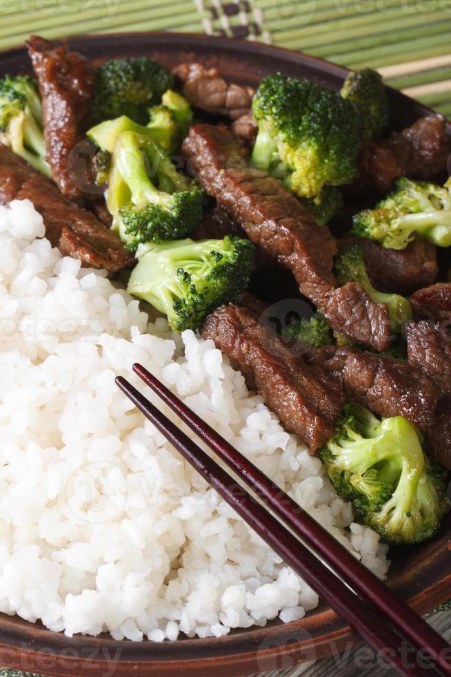 rundvlees met broccoli en rijst macro, eetstokjes. verticaal bovenaanzicht foto