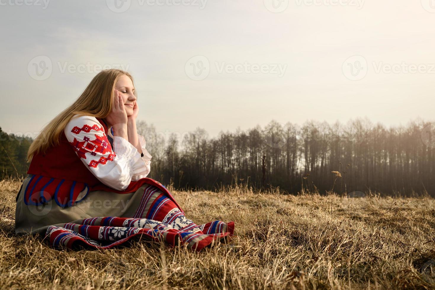 jonge vrouw in Slavische Wit-Russische nationale oorspronkelijke pak buitenshuis foto