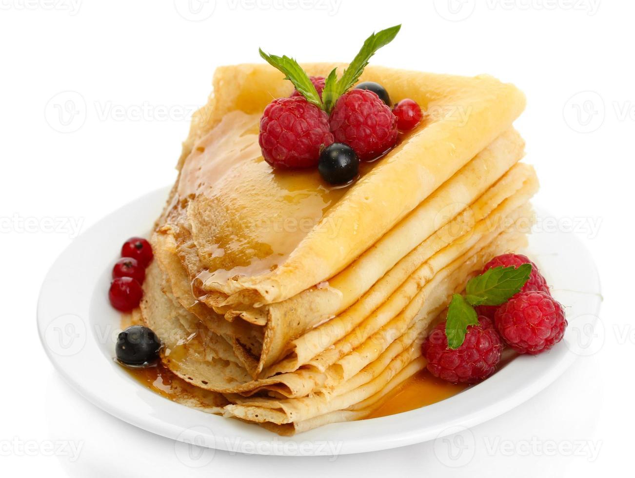 heerlijke pannenkoeken met bessen en honing op wit wordt geïsoleerd foto