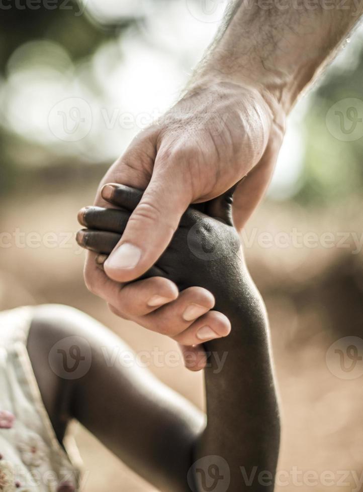 Afrikaanse childs hand die een witte volwassenenhand houdt foto