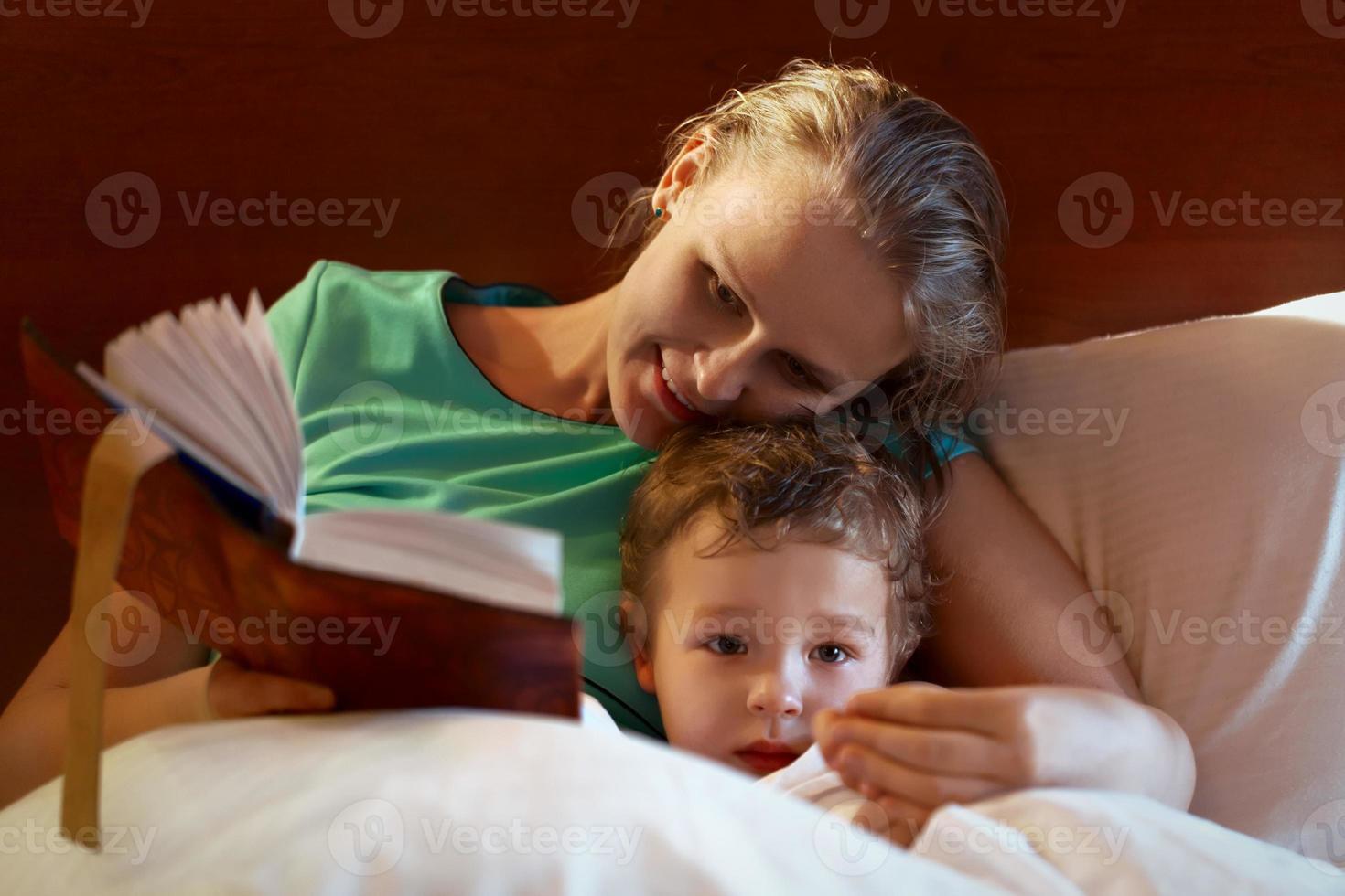 jonge moeder die aan haar kind in bed leest foto