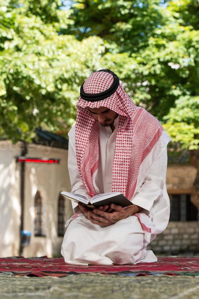 moslim man in dishdasha leest de koran foto
