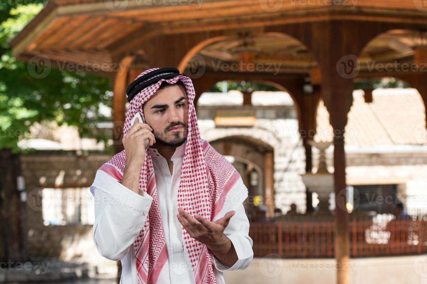 knappe man van het Midden-Oosten praten op mobiele telefoon foto