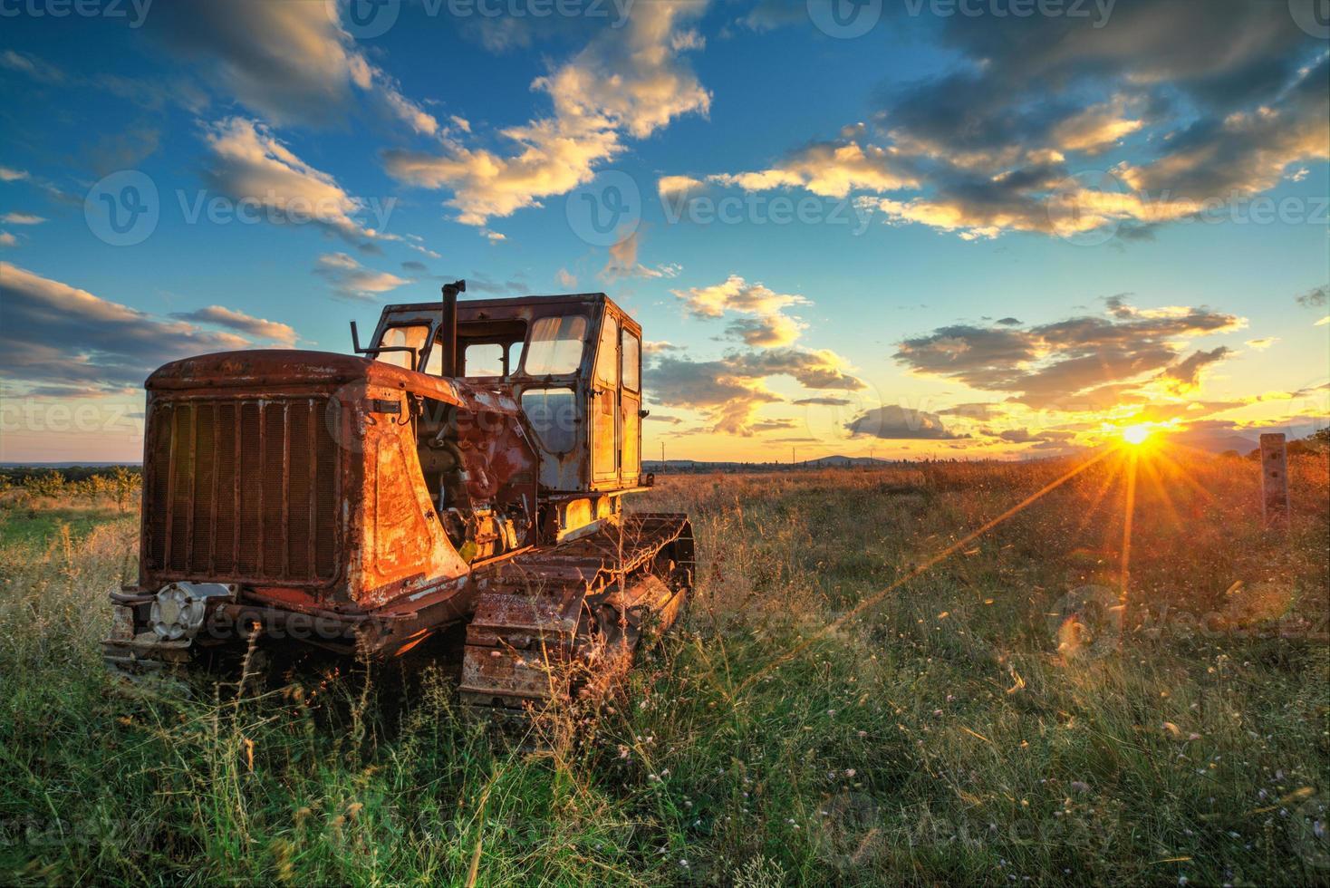 oude roestige trekker in een veld op zonsondergang foto