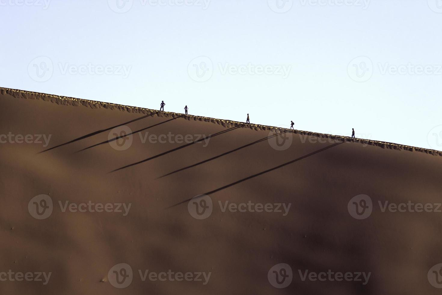 mensen op een rode duin in Sossusvlei, Namibië foto