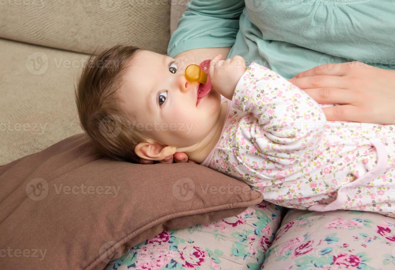 baby spelen met fopspeen liggend op de benen van de moeder foto