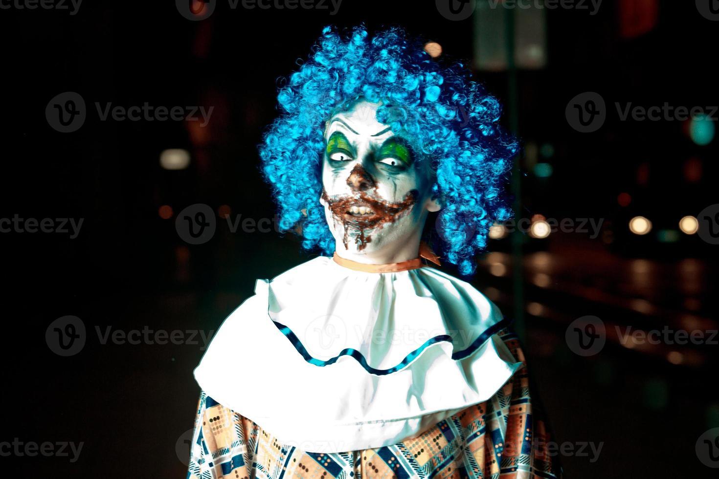 gekke boze clown in de stad op halloween die mensen bang maakt foto