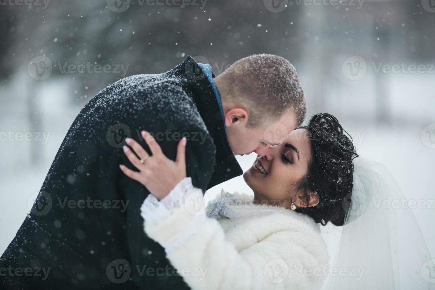 bruid en bruidegom lopen op de stad in de sneeuw foto
