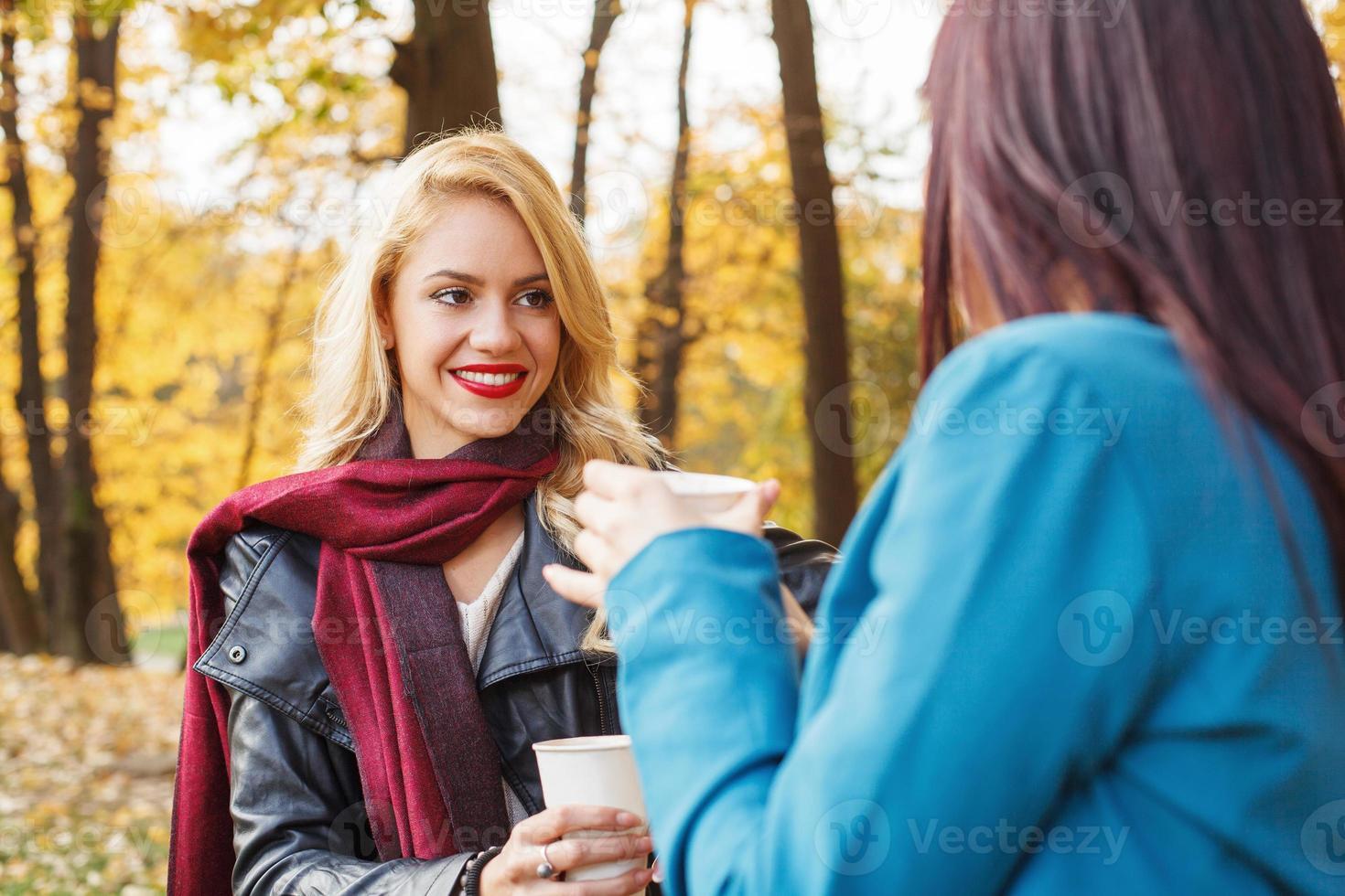 twee vrouwen die koffie drinken in het park foto