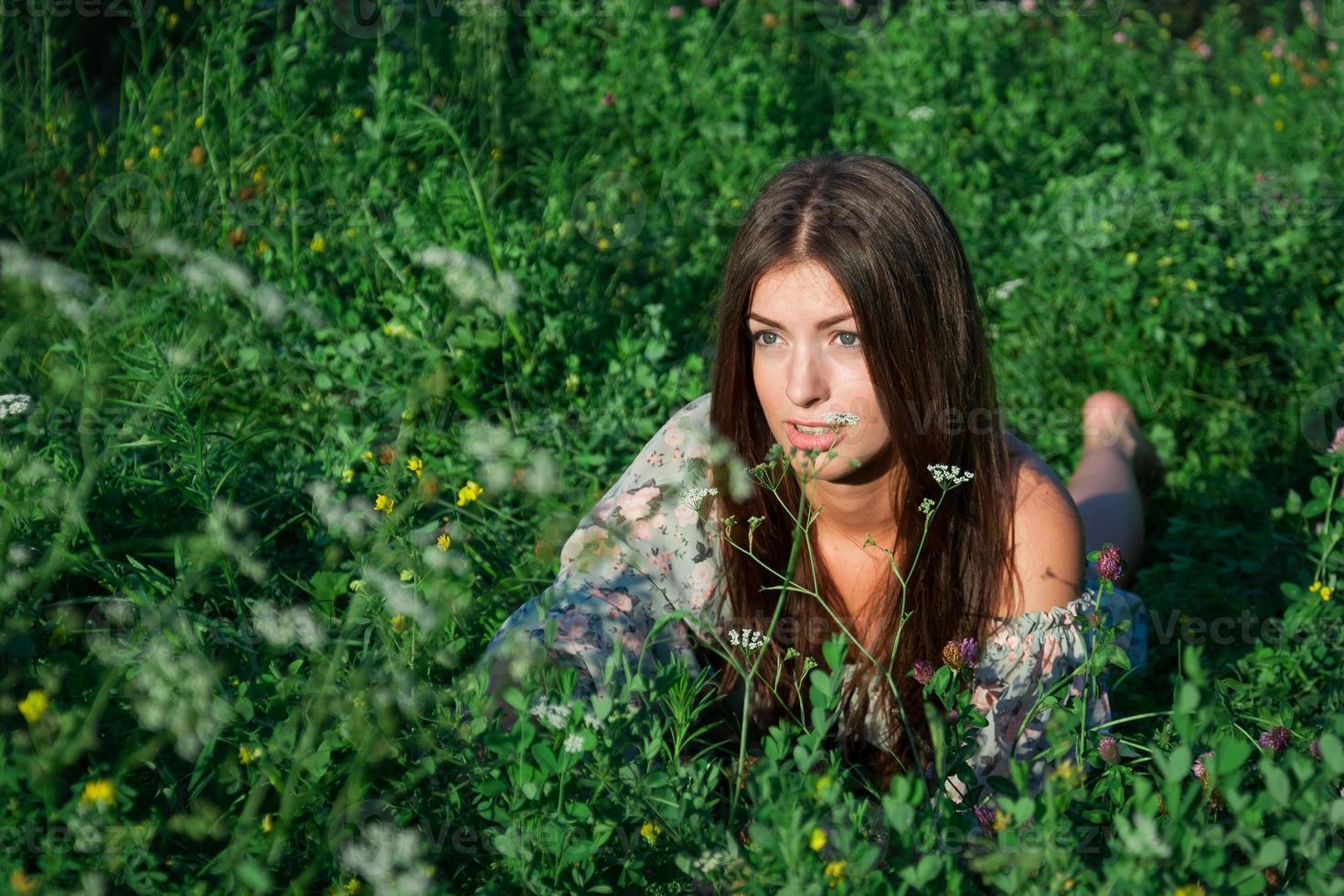 leuk meisje tussen groen gras en bloemen foto