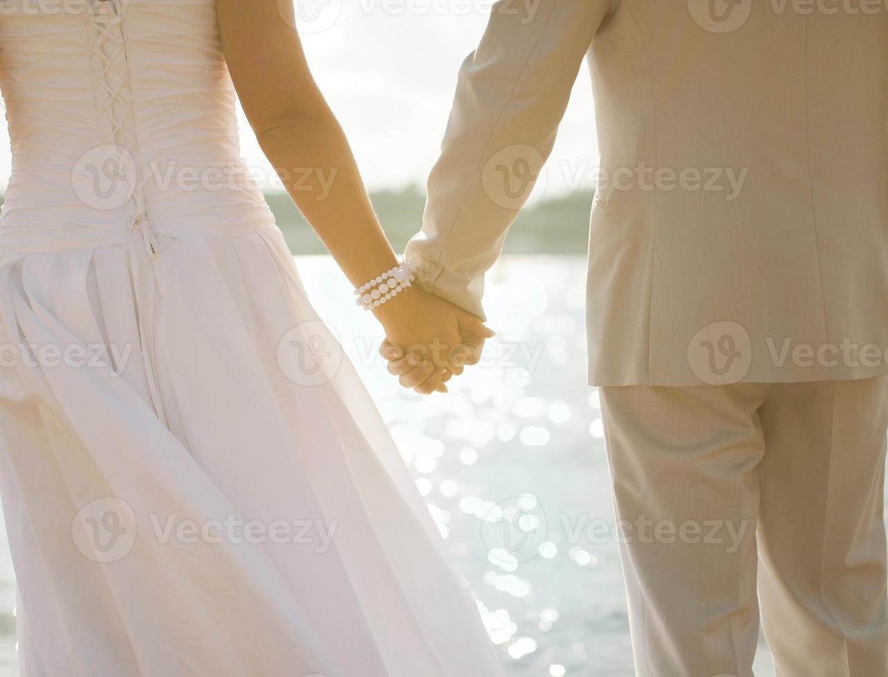 bruid en bruidegom hand in hand foto