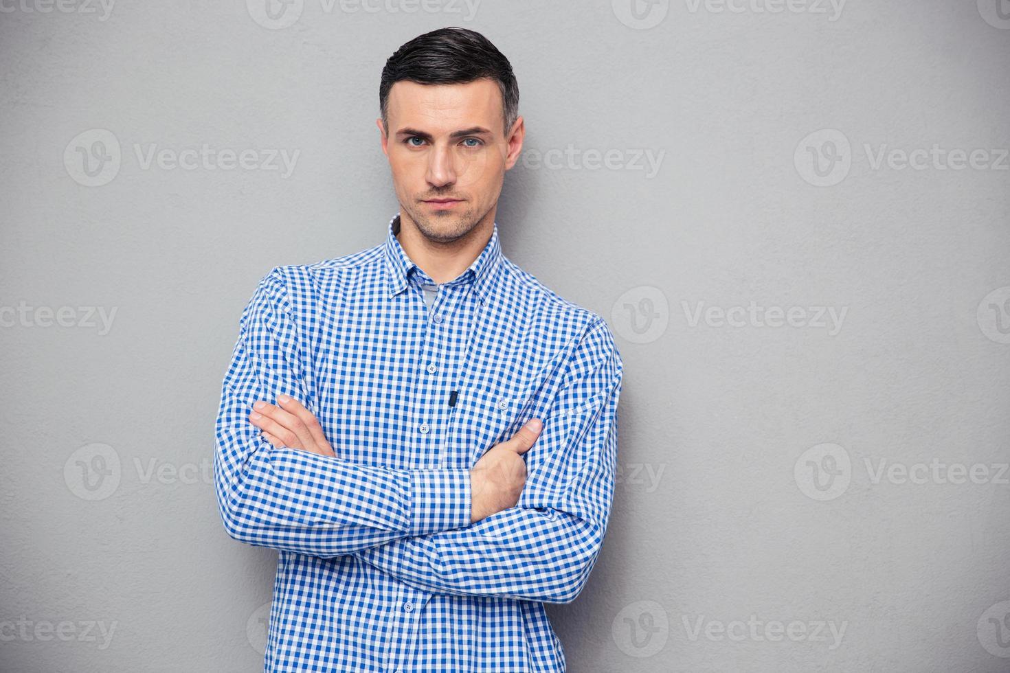 portret van een knappe jonge man met gevouwen armen foto