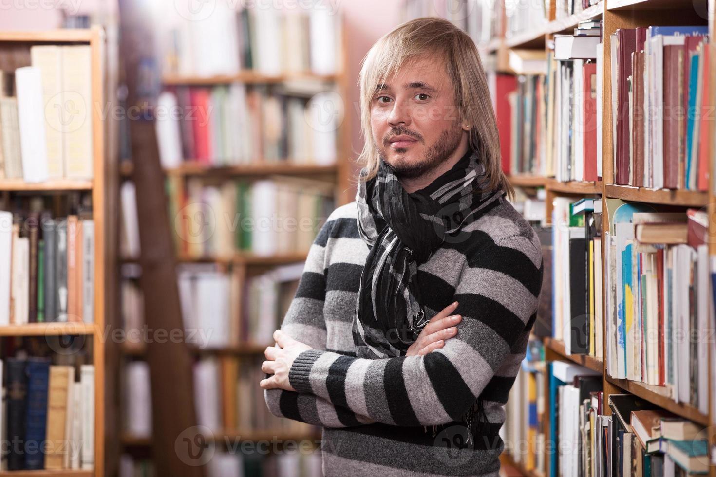 portret van knappe man in bibliotheek foto