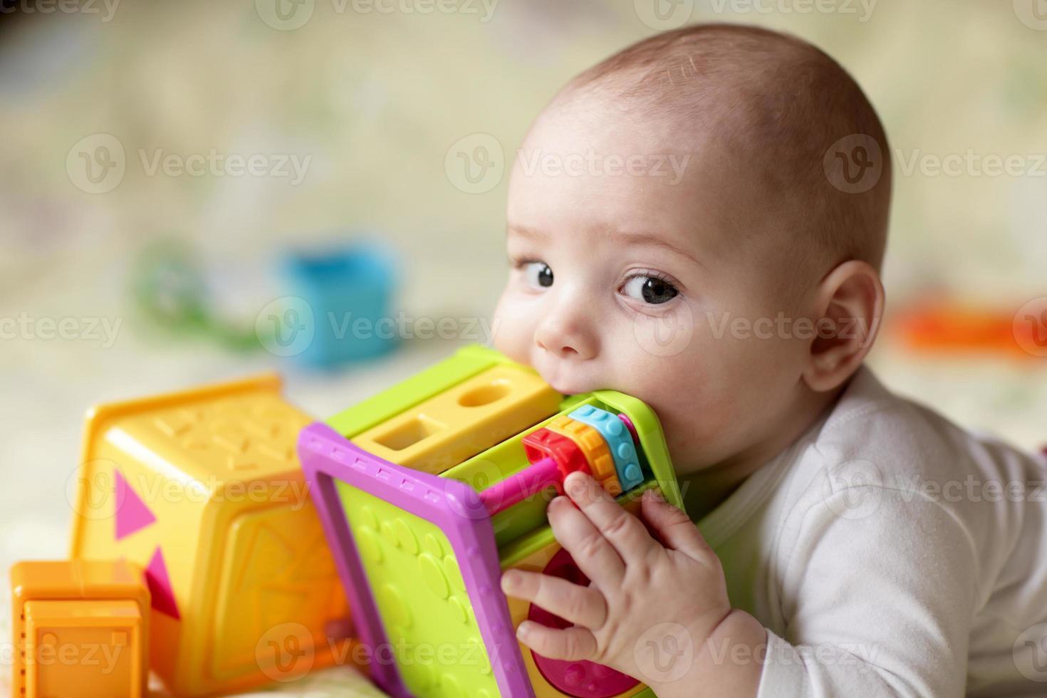 jongen bijten speelgoed foto