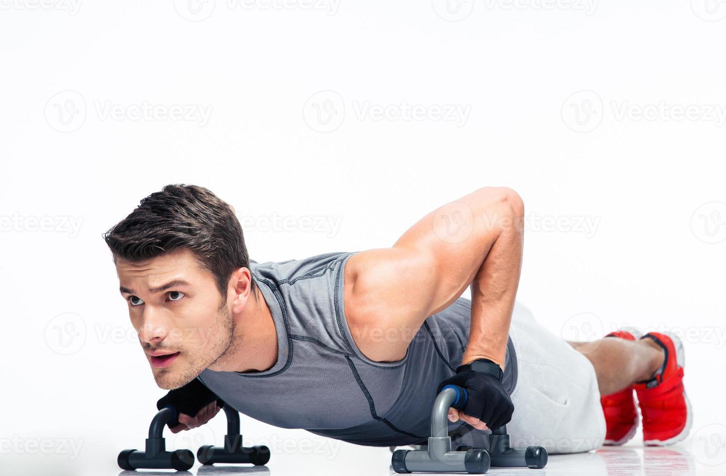 fitness jonge man doet push-ups foto