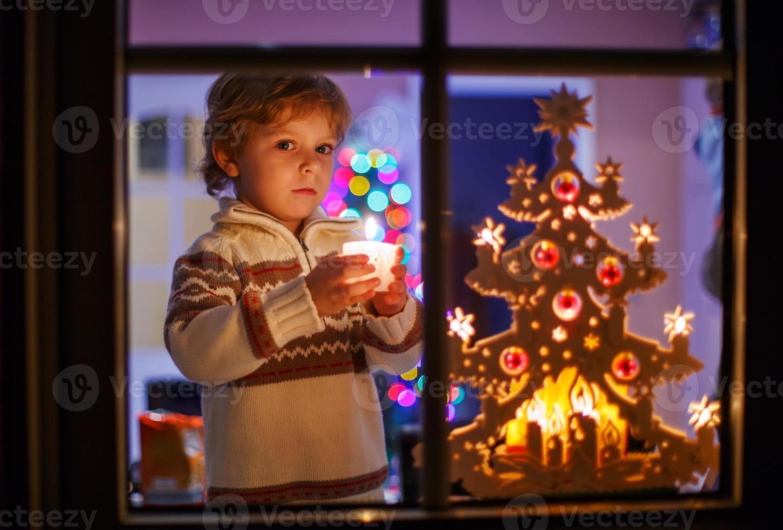 gelukkig klein kind permanent door raam op Kerstmis foto