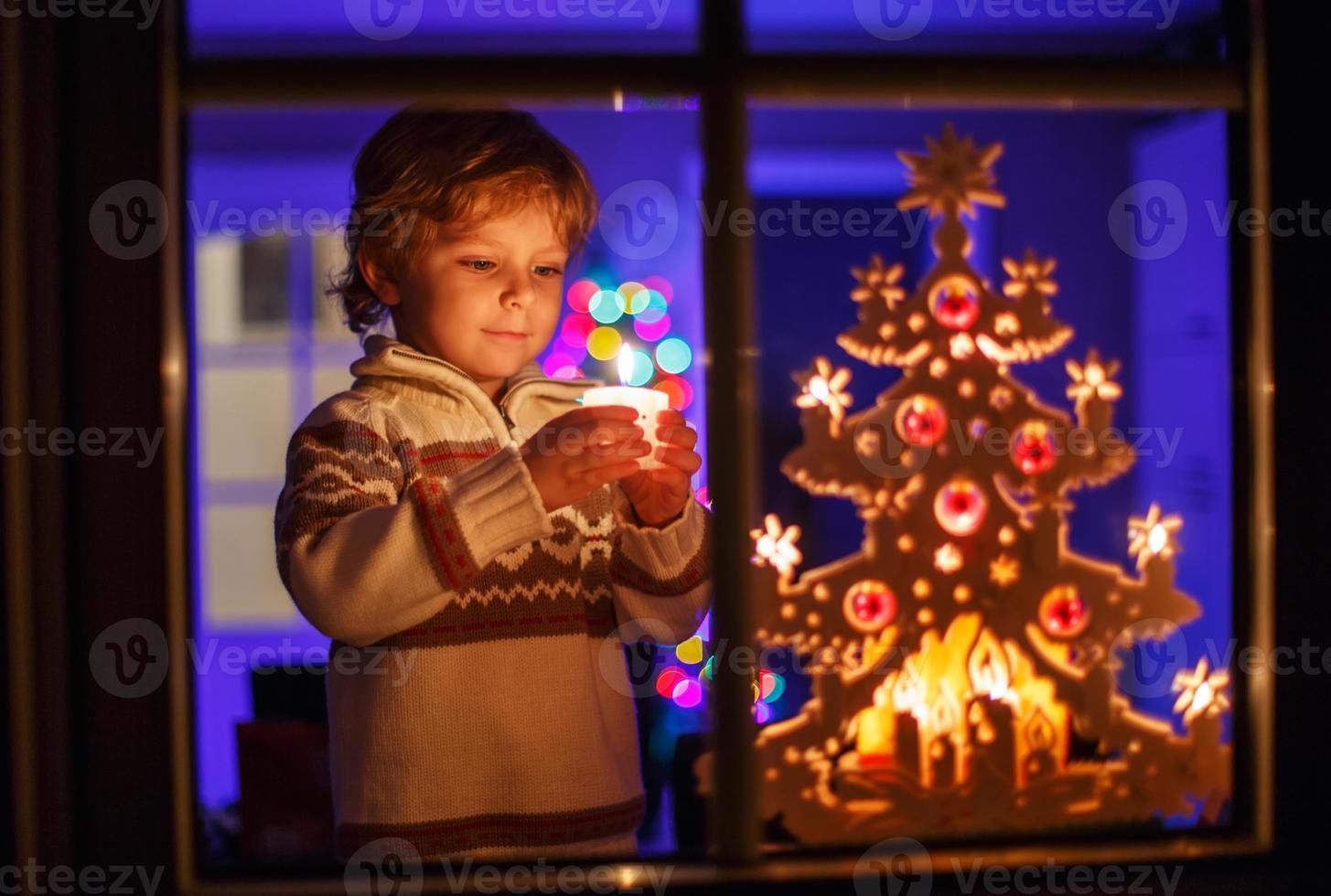 glimlachende jongen die zich door venster bij Kerstmis bevindt foto