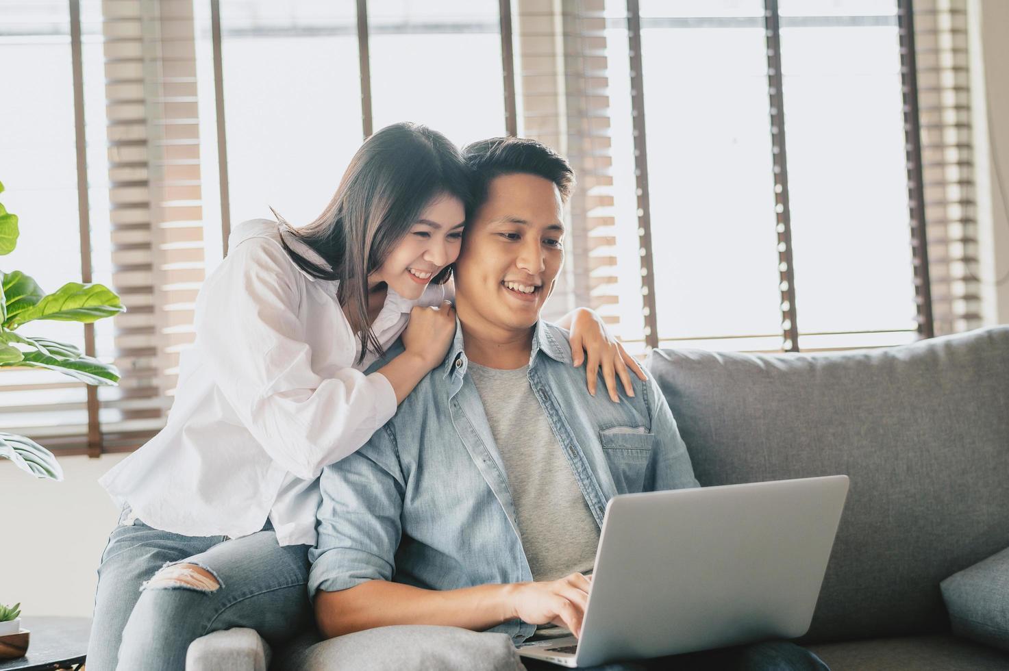 Aziatisch paar dat laptop op bank thuis met behulp van foto