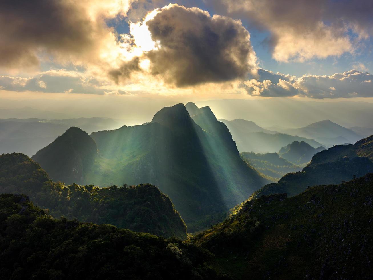 zon schijnt door wolken en bergen foto