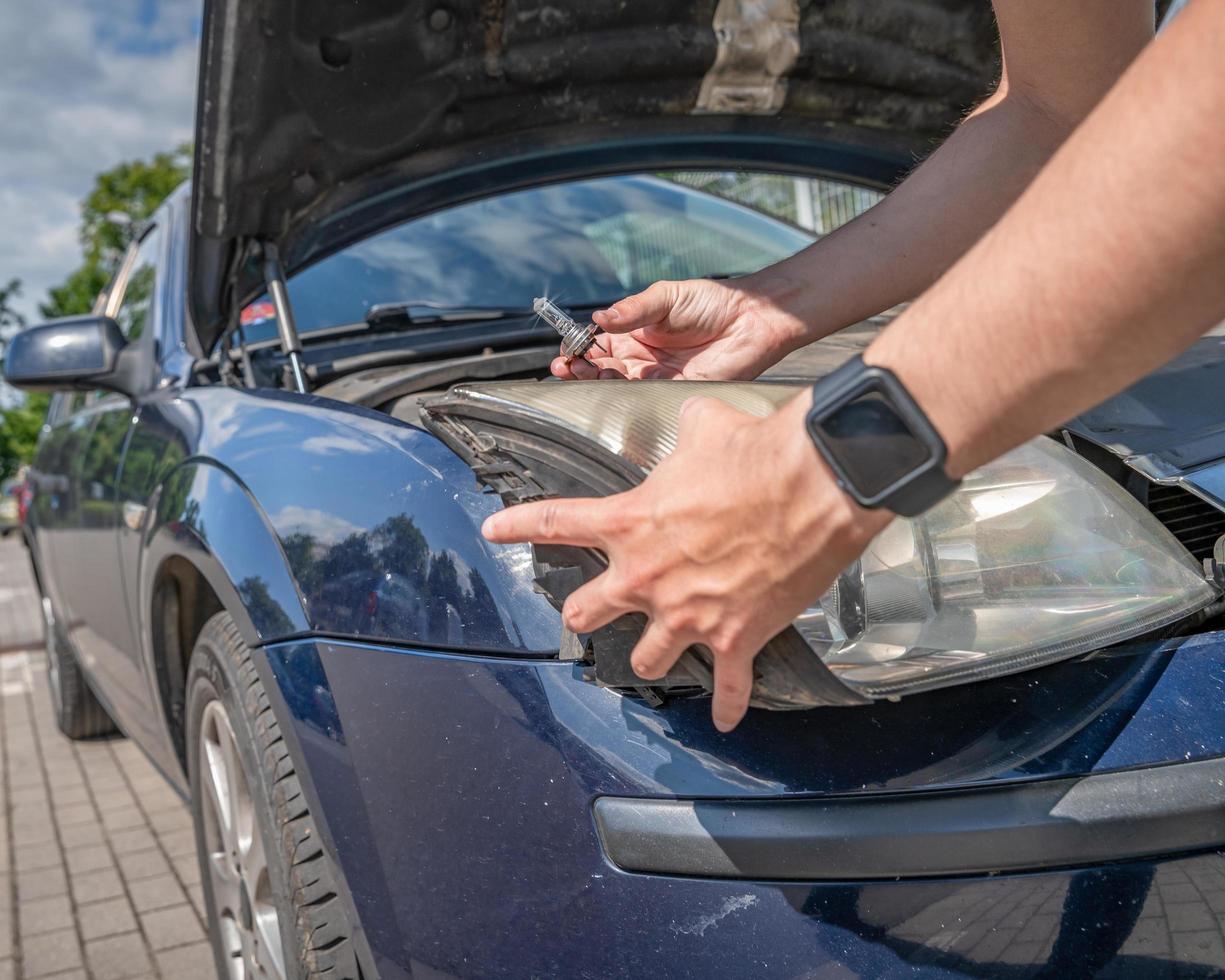 autobezitter verandert koplamp foto