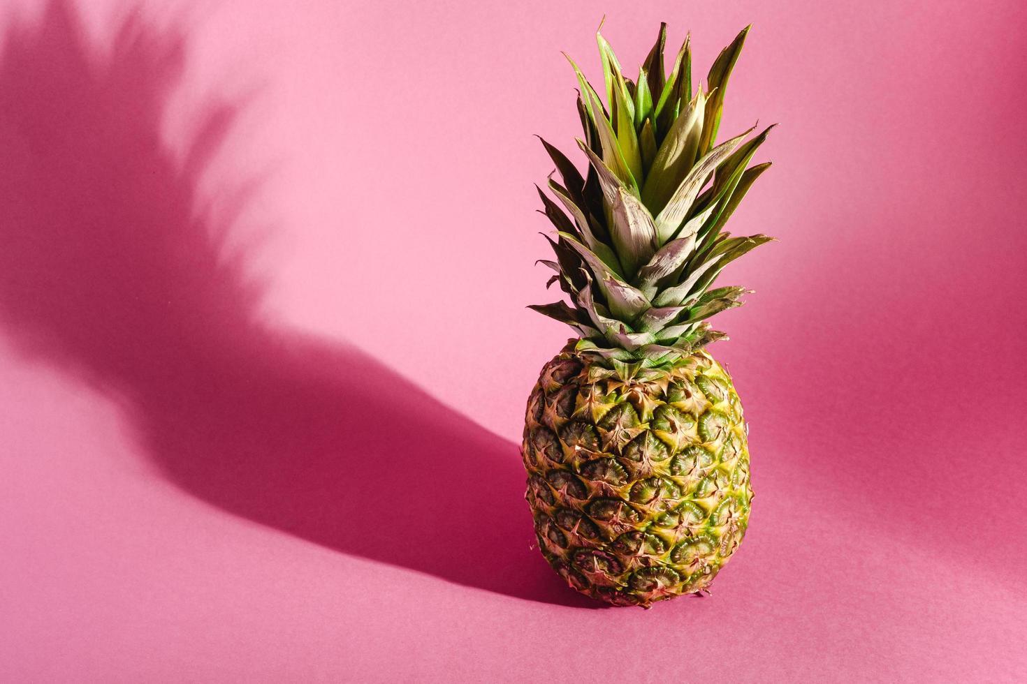 ananas op roze paarse achtergrond met harde schaduw foto
