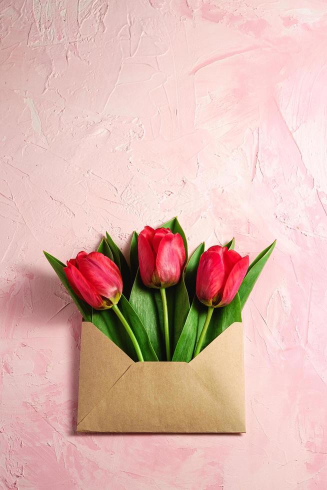 rode tulp bloemen in papieren envelop op gestructureerde roze achtergrond foto