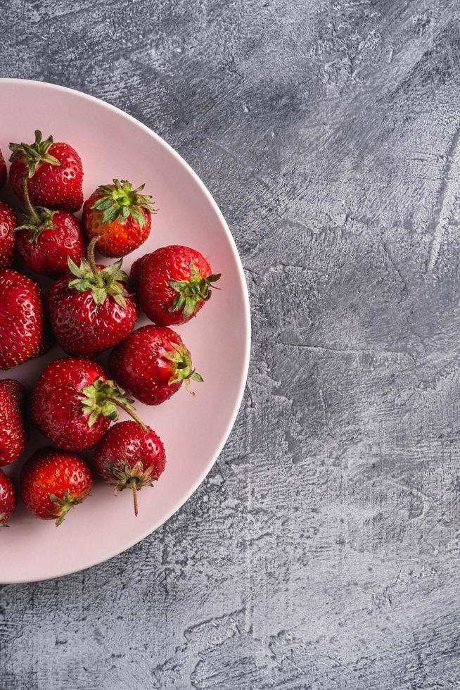 rijpe aardbeien op plaat tegen grijze stenen achtergrond foto