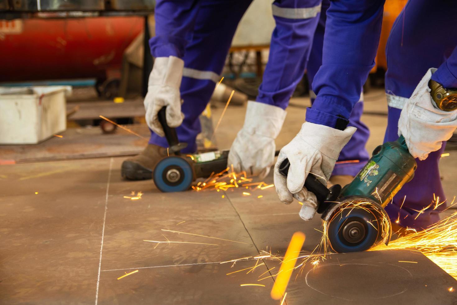 twee arbeiders snijden metalen platen met een elektrische slijpmachine foto