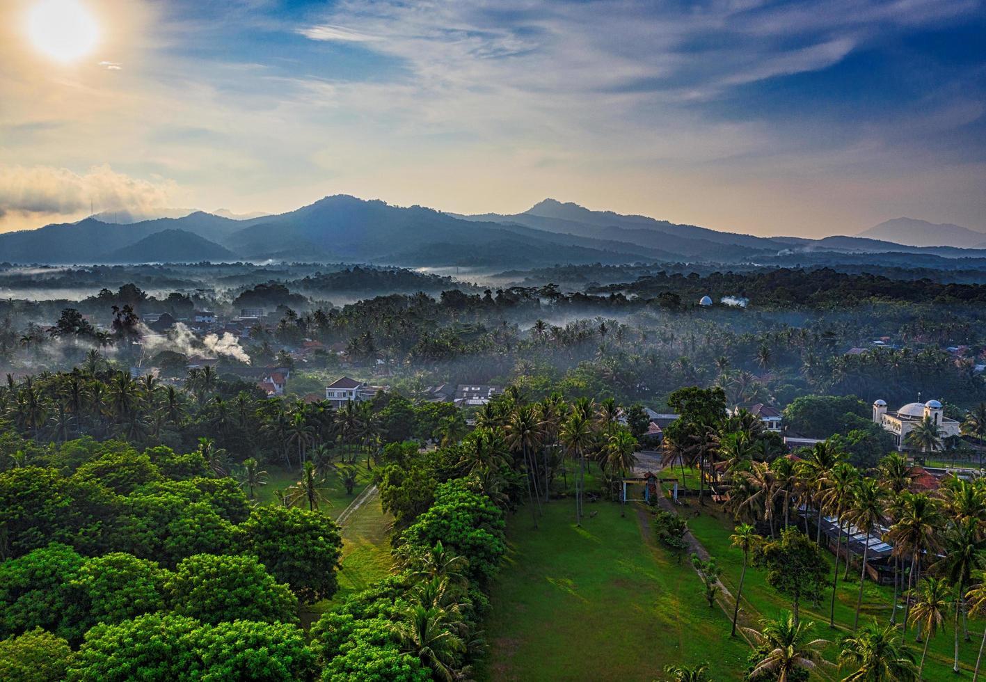 ondergaande zon over stad in Indonesië foto
