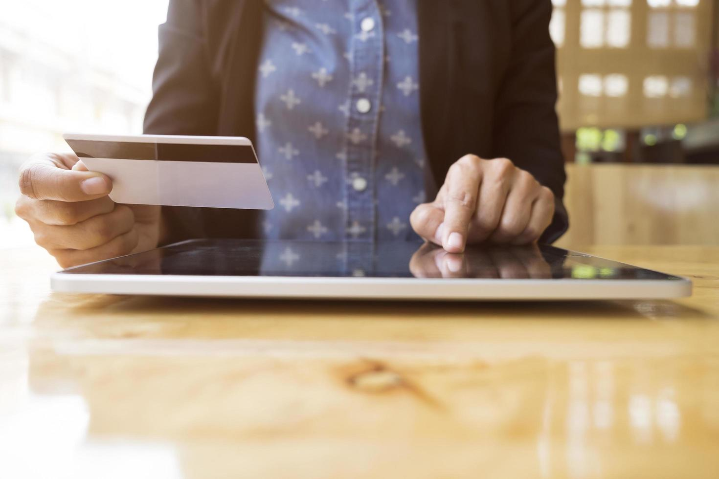 een vrouw zit aan een bureau om online boodschappen te doen foto