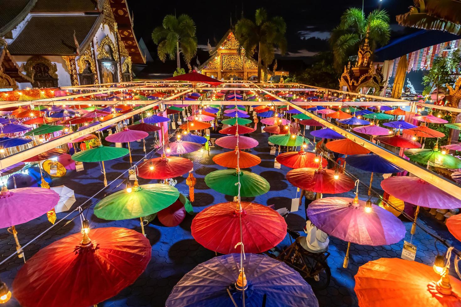 heldere kleurrijke papieren vintage lantaarns opgehangen in de buurt van een boeddhistische tempel in thailand foto