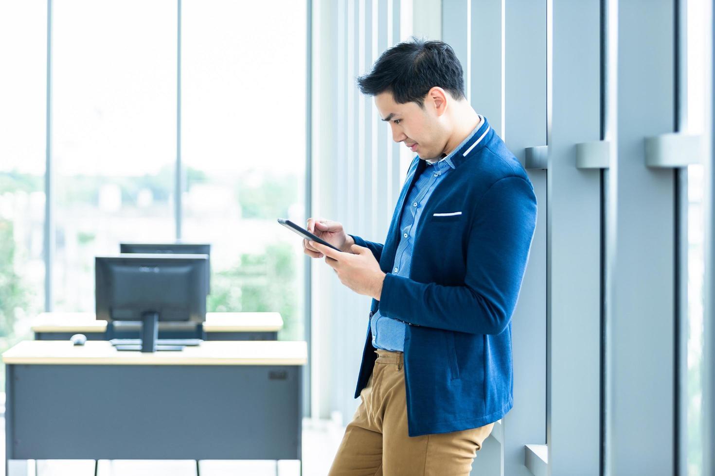 jonge Aziatische ondernemer met behulp van mobiele tablet op het werk foto