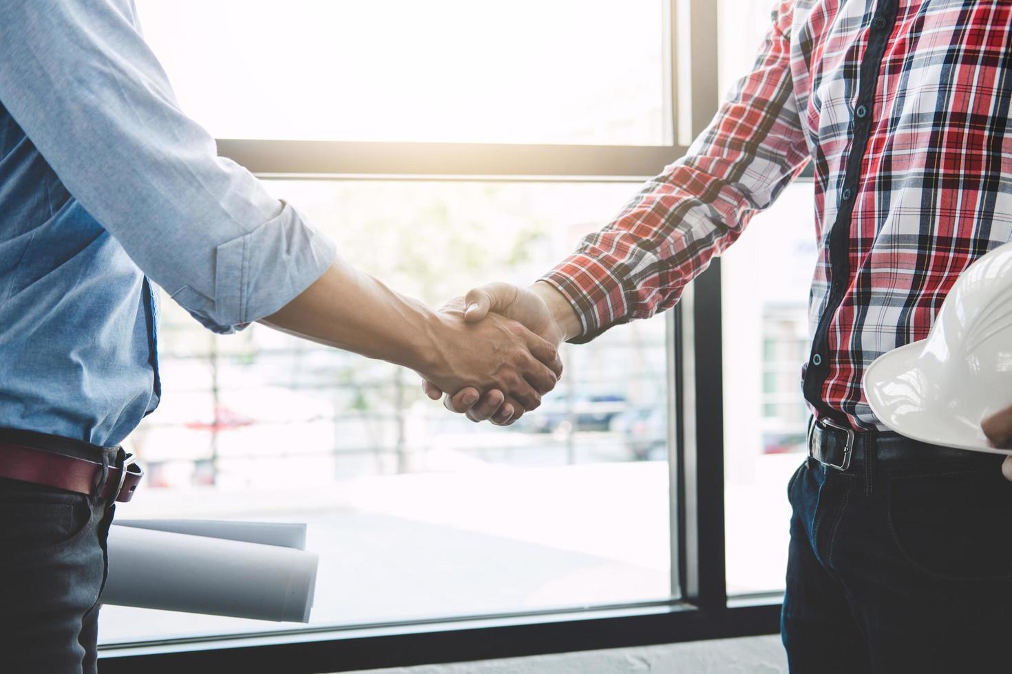 twee ingenieurs ontmoeten elkaar voor project, handdruk na overleg foto