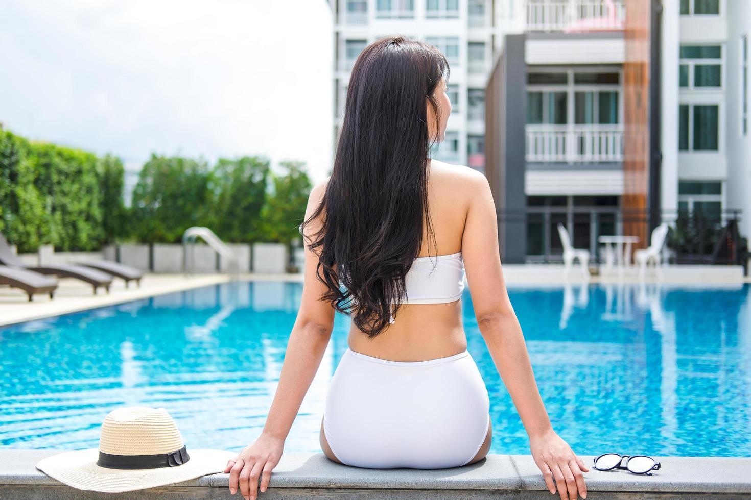 vrouw zitten aan de zijkant van een zwembad foto