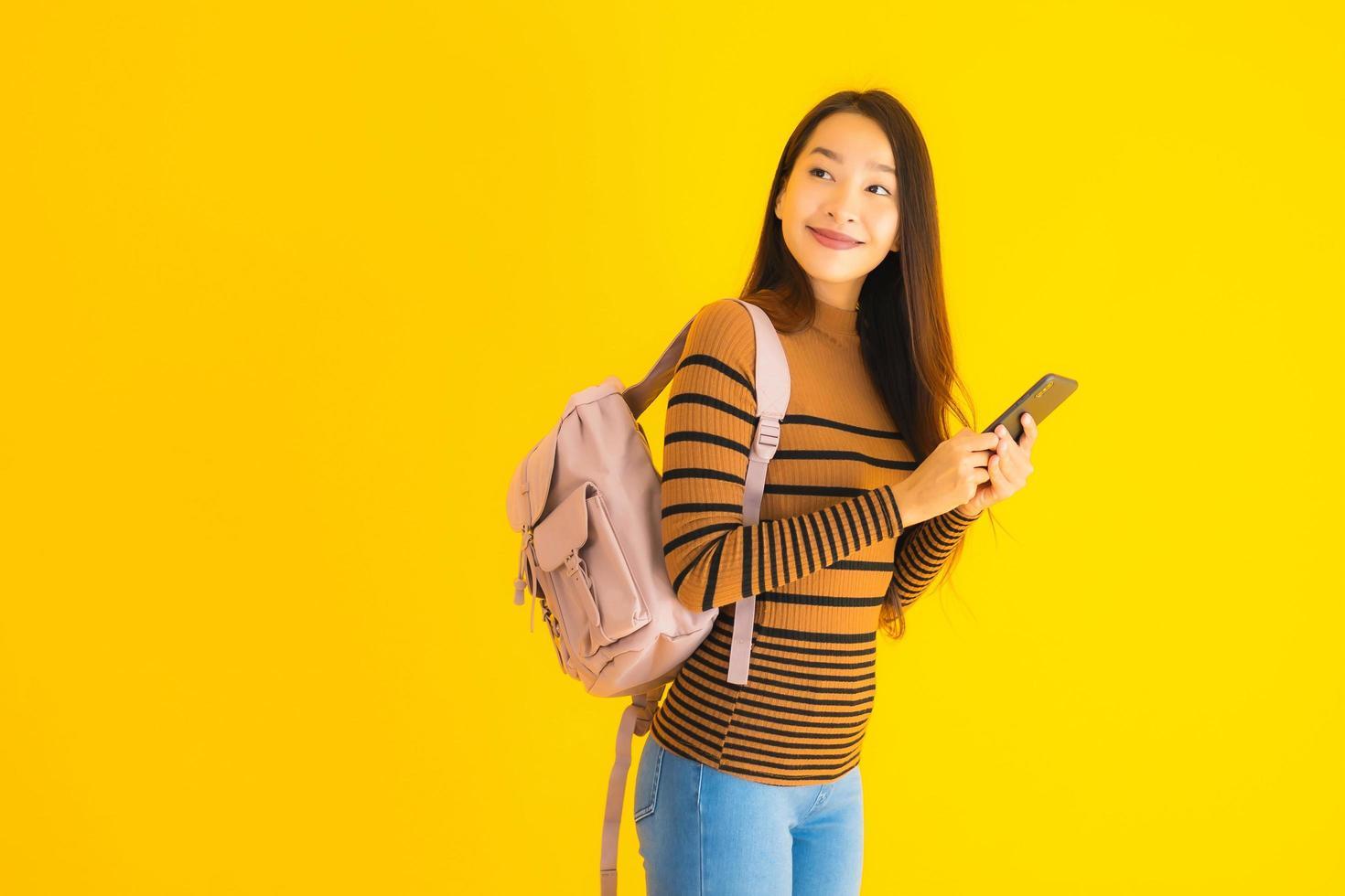 Aziatische vrouw met rugzak en smartphone foto