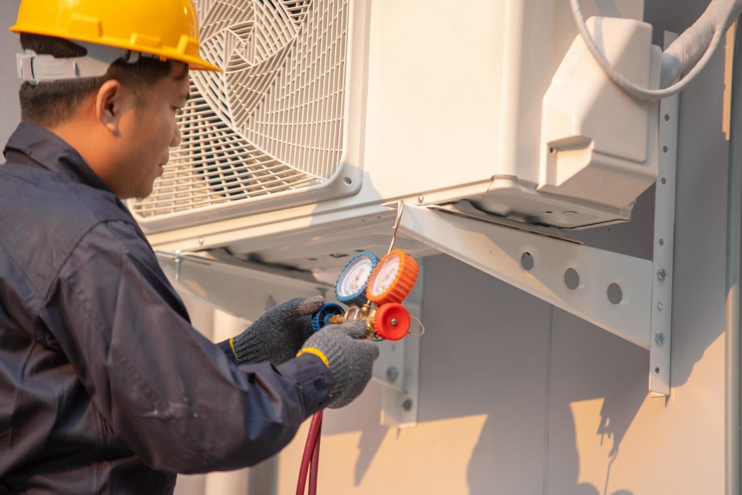 technicus controleert buitenunit, meetapparatuur voor het vullen van airconditioners. foto
