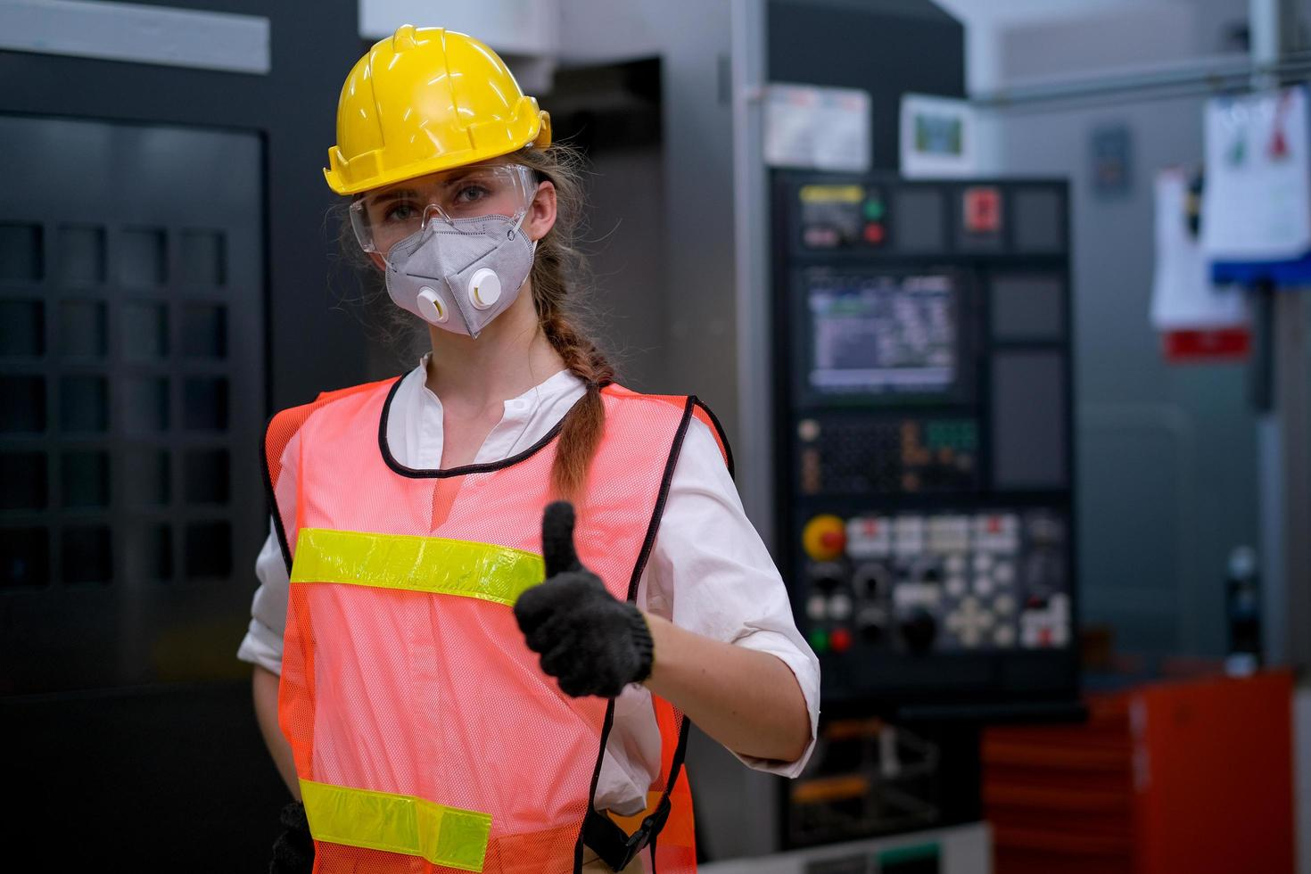 jonge vrouwelijke technicus draagt een beschermend masker op het werk foto