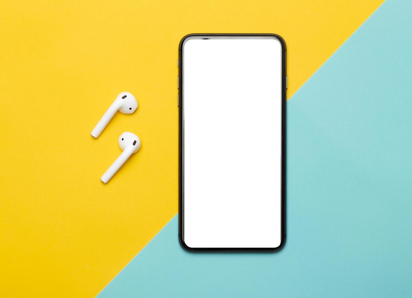 smartphone en oordopjes op gele en blauwe achtergrond foto