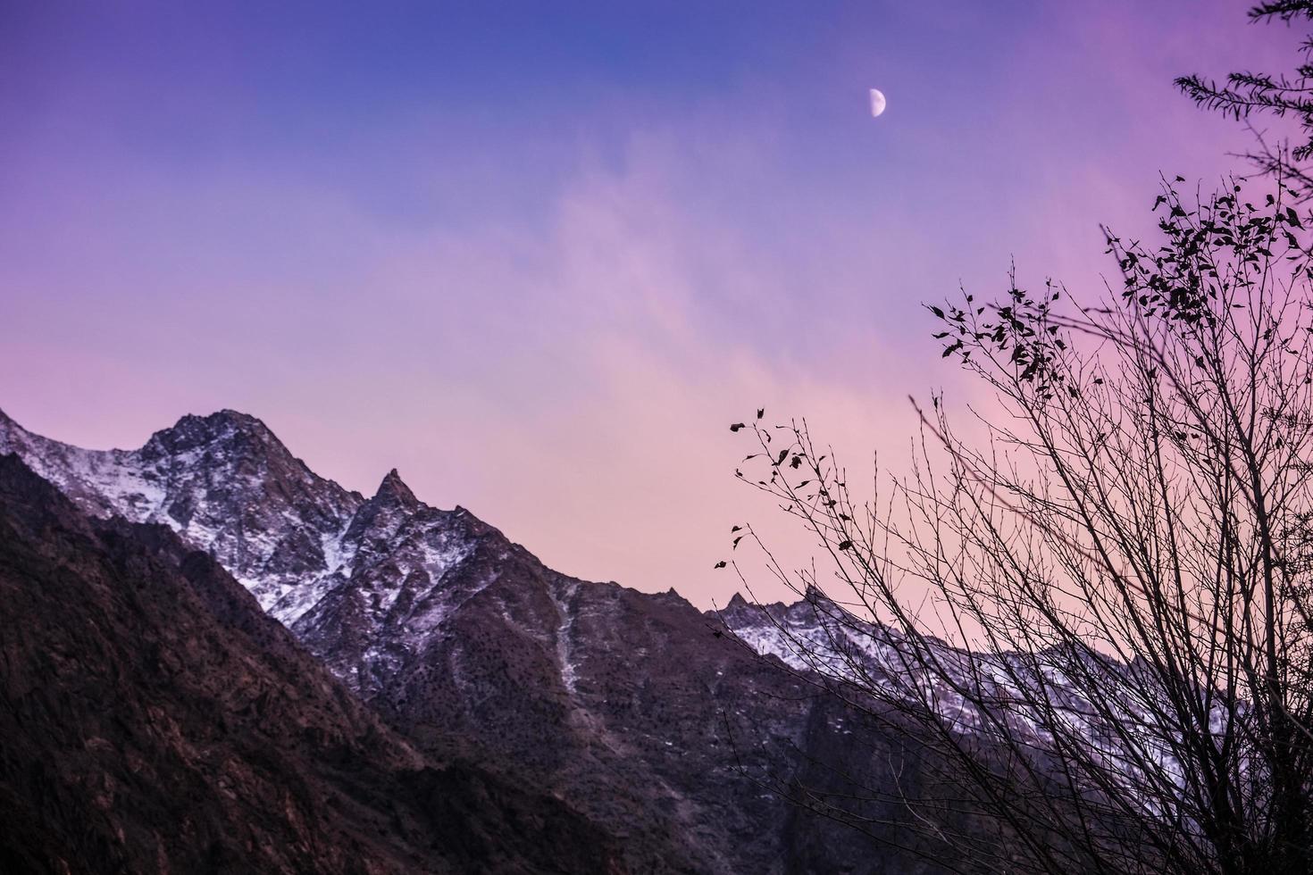 schemering hemel met maan stijgt boven besneeuwde bergen foto