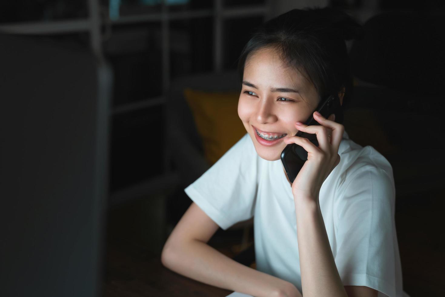 Aziatische vrouw die op celtelefoon spreekt foto