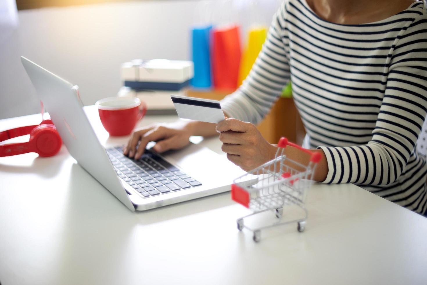 vrouwenzitting bij computer die online winkelt foto