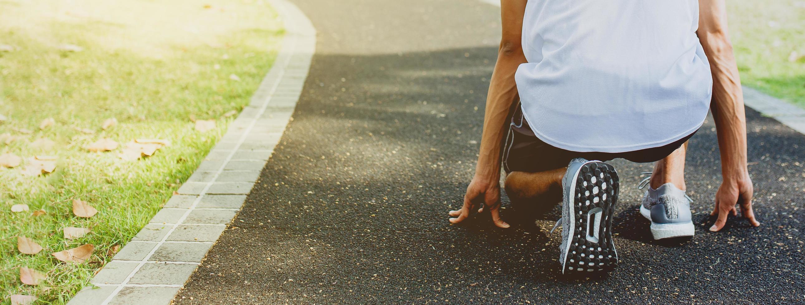 atleet in het runnen van start pose in openbaar park foto