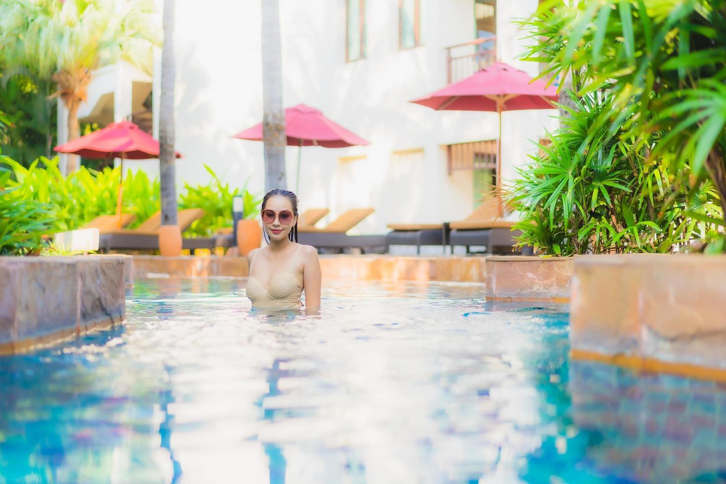 portret mooie jonge Aziatische vrouw ontspannen rond het zwembad in het hotel resort foto