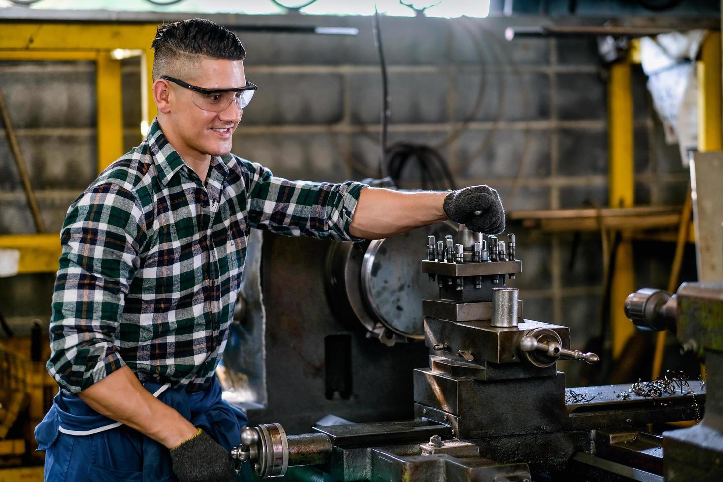 een ingenieur die een veiligheidsbril draagt, werkt aan een machine foto