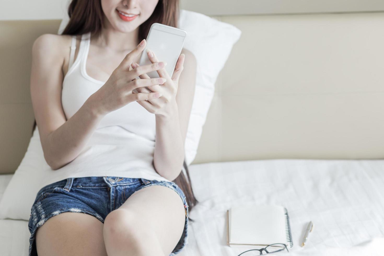 close-up van smartphone van de vrouwenholding in bed foto