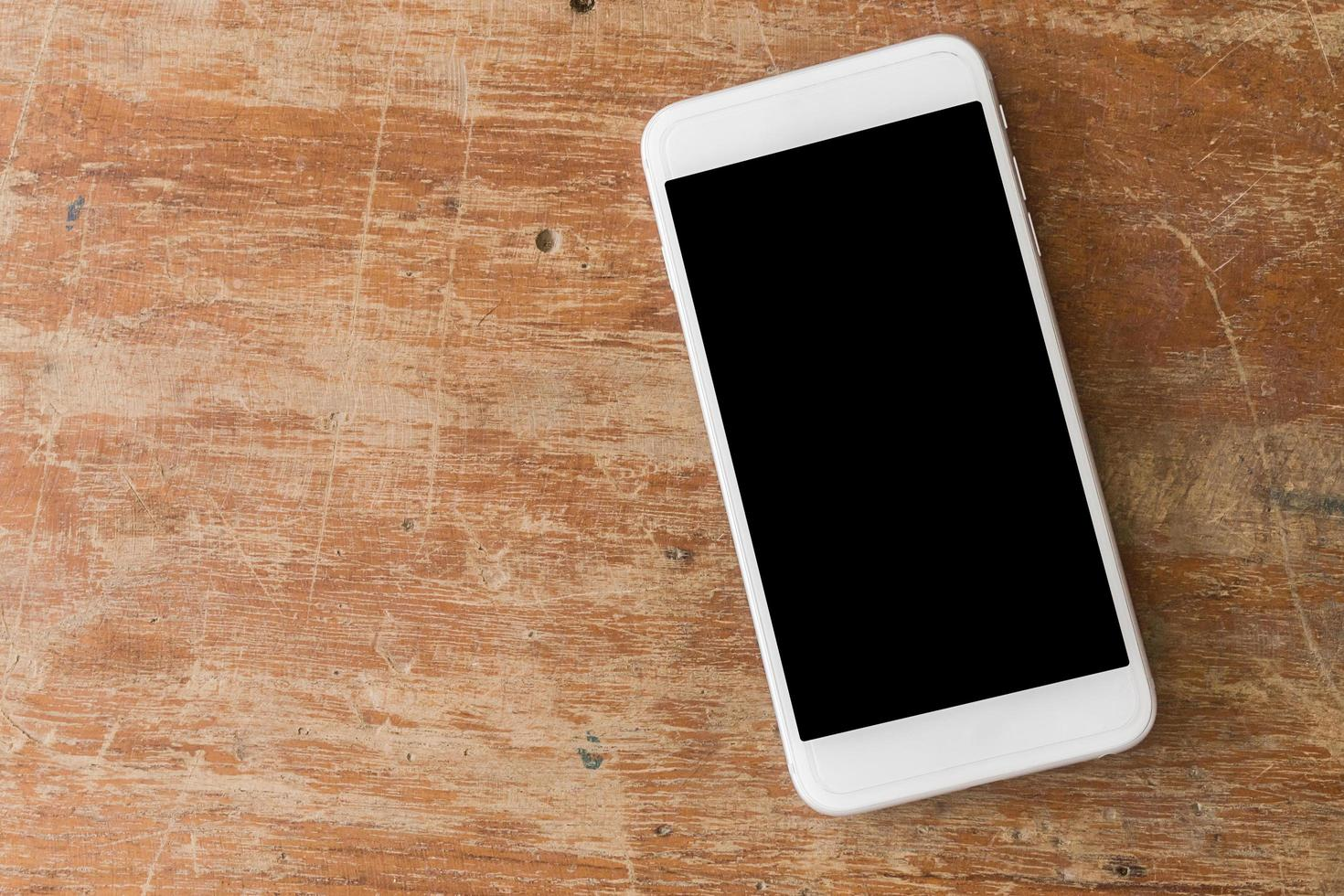 witte mobiele telefoon op houten tafel foto