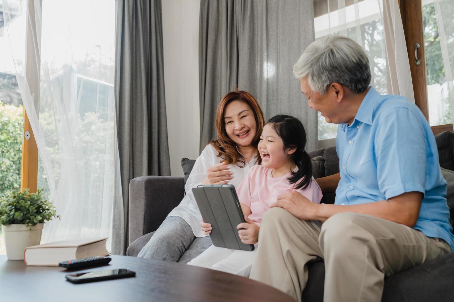 Aziatische grootouders en kleindochter met behulp van tablet thuis foto
