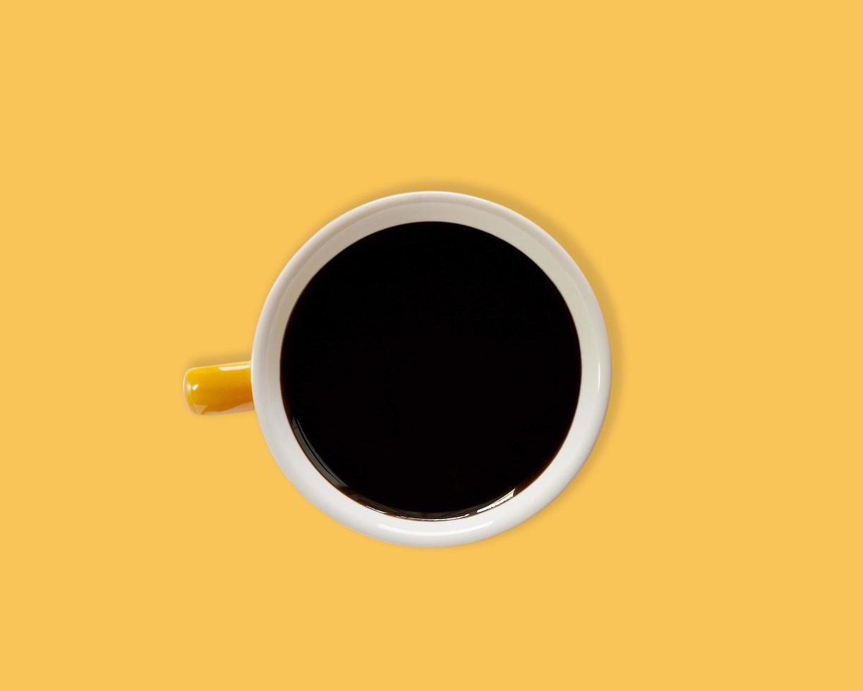 zwarte koffie in een fel oranje kopje foto