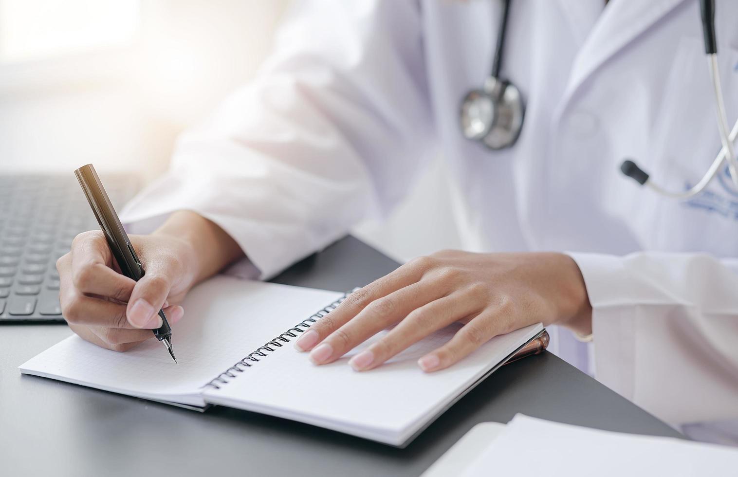 vrouwelijke arts die op notitieboekje schrijft foto