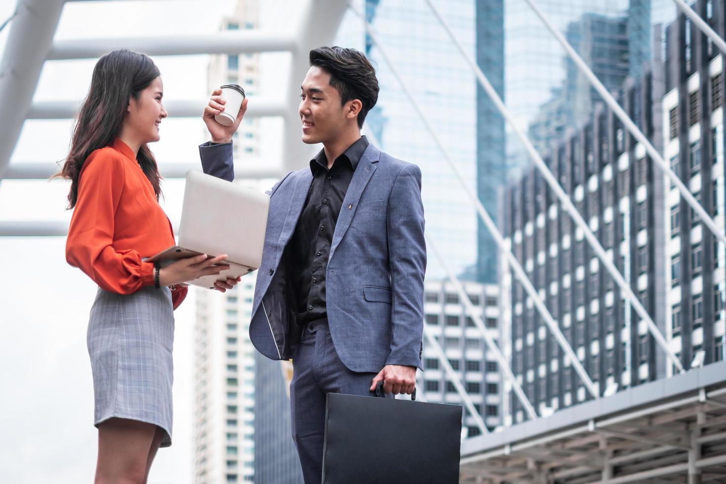 twee zakenmensen verzamelen zich buiten hun kantoor foto